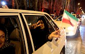 A woman in a car flashes the 'V for Victory' sign and waves an Iranian flag as people celebrate on Valiasr street in northern Tehran on April 2 after...