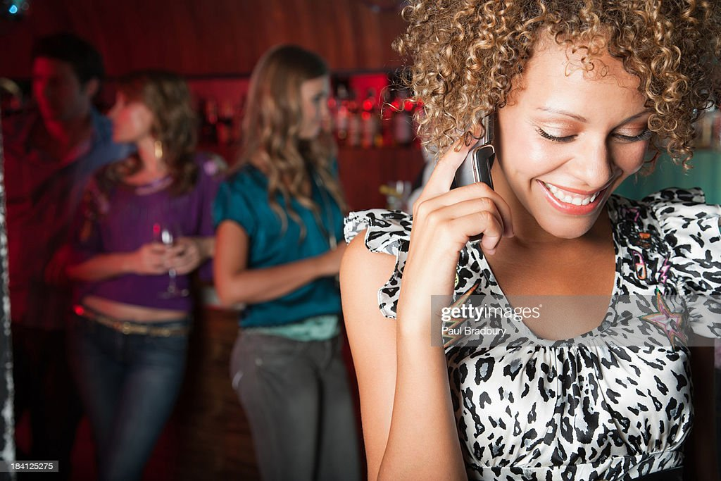 A woman in a club on her cellular phone : Stock Photo