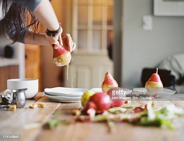A woman in a domestic kitchen cooking. Dipping fresh organic pears into a sauce for dessert. Fresh ingredients. Brown sugar cubes
