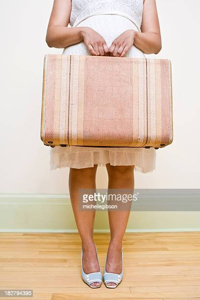 Woman in a dress holding a pale pink suitcase