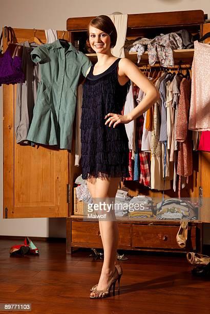 Woman in a dress in front of cupboard