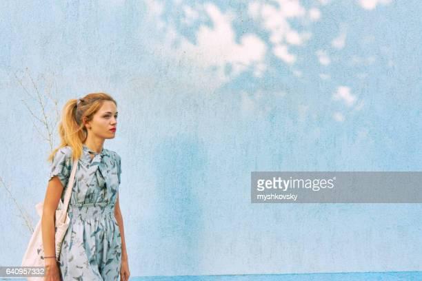 Frau in einem Kleid in der Nähe der Wand