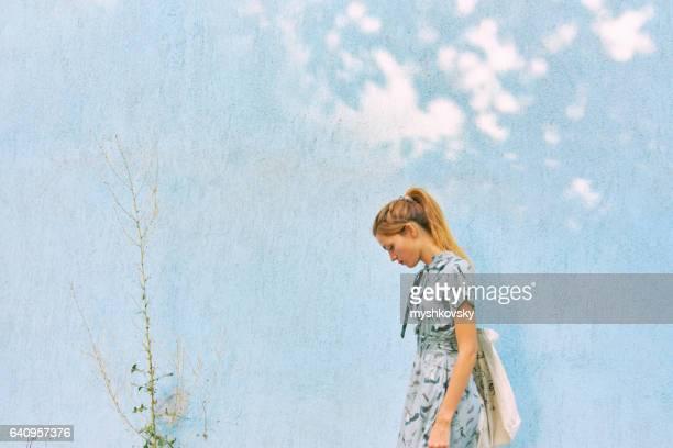Vrouw in een jurk in de buurt van de muur