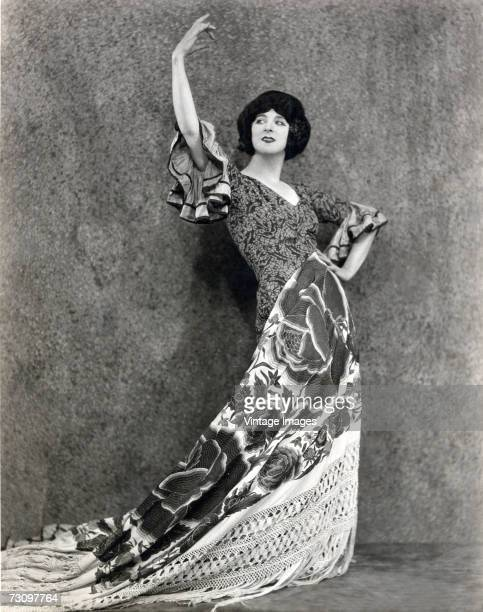 A woman in a dress poses in a graceful curve to suggest flamenco dancing early 20th Century