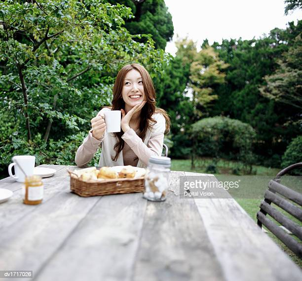 Woman in a Garden, Sitting at the End of a Wooden Table and Holding a Coffee Cup, with Pastry and Food Jars Around Her