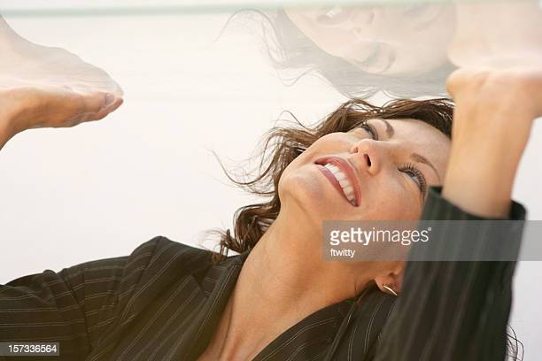 Woman in a glass box trying to get out by punching the roof