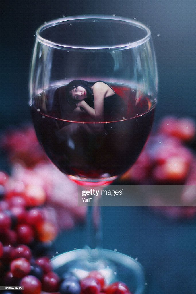 Woman in a glass of red wine : Stock Photo