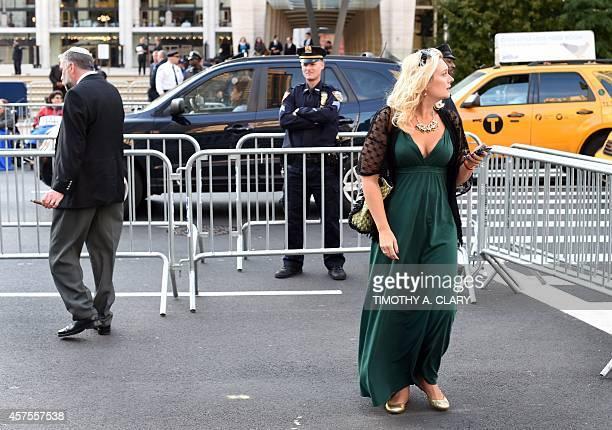 A woman in a gown walks away as demonstrators protest outside Lincoln Center on October 20 2014 to criticize The Metropolitan Opera's planned...