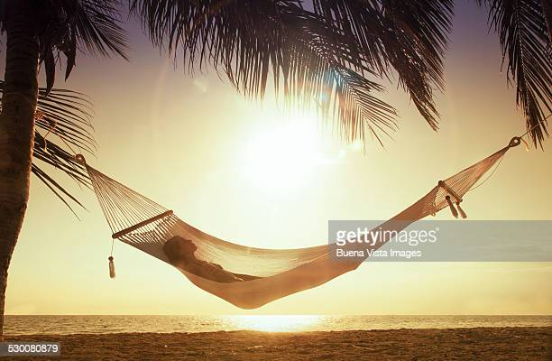 Woman in a hammock at sunset