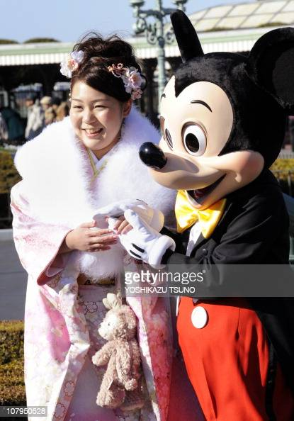 A woman in a kimono is greeted by Disney character Mickey Mouse to celebrate the annual 'ComingofAge Day' ceremony at the Tokyo Disneyland amusement...