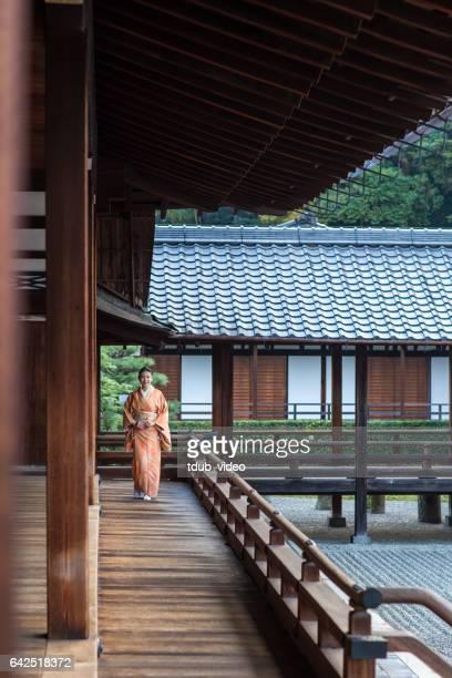 Woman in a kimono walking through a temple corridor