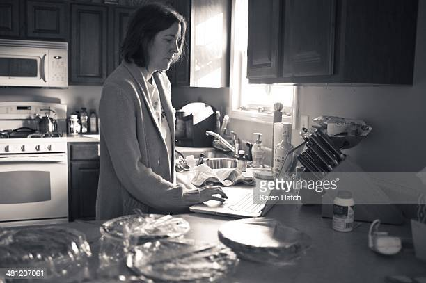 A woman in a kitchen works on her laptop computer in morning sunlight