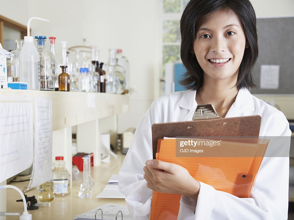 Woman in a laboratory holding a clipboard : Stock Photo
