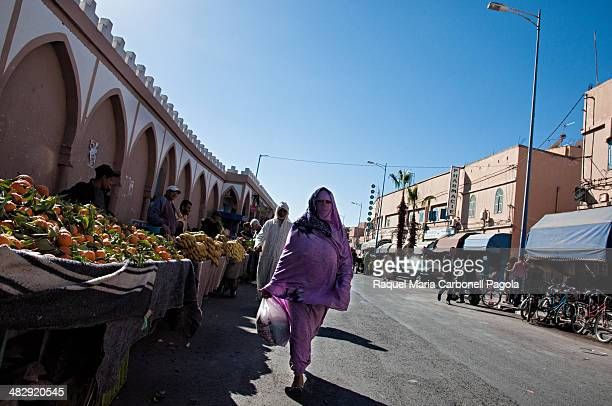 Woman in a Moroccan niqab walking on the streets of the market area in the ancient Medina