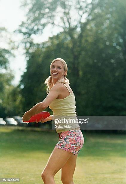 Woman in a Park Preparing to Throw a Red Frisbee