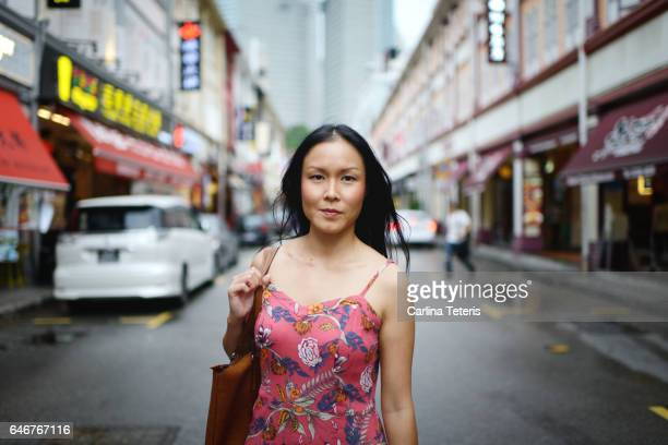 Woman in a pink floral dress standing in the middle of the street