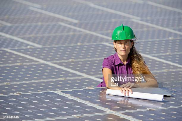 Woman in a purple shirt on top of multiple solar panels