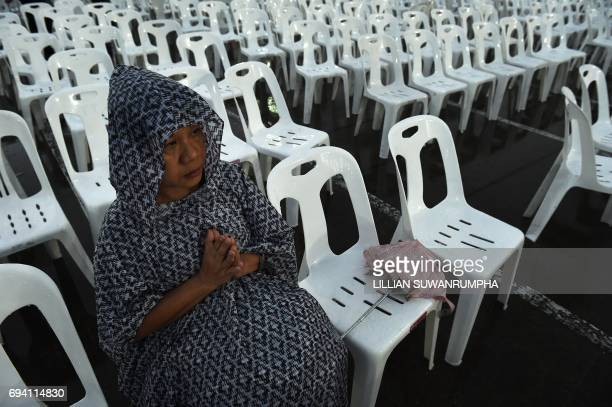 A woman in a raincoat prays during a Buddhist ceremony for the late Thai King Bhumibol Adulyadej at the King Rama V Monument in Bangkok on June 9...