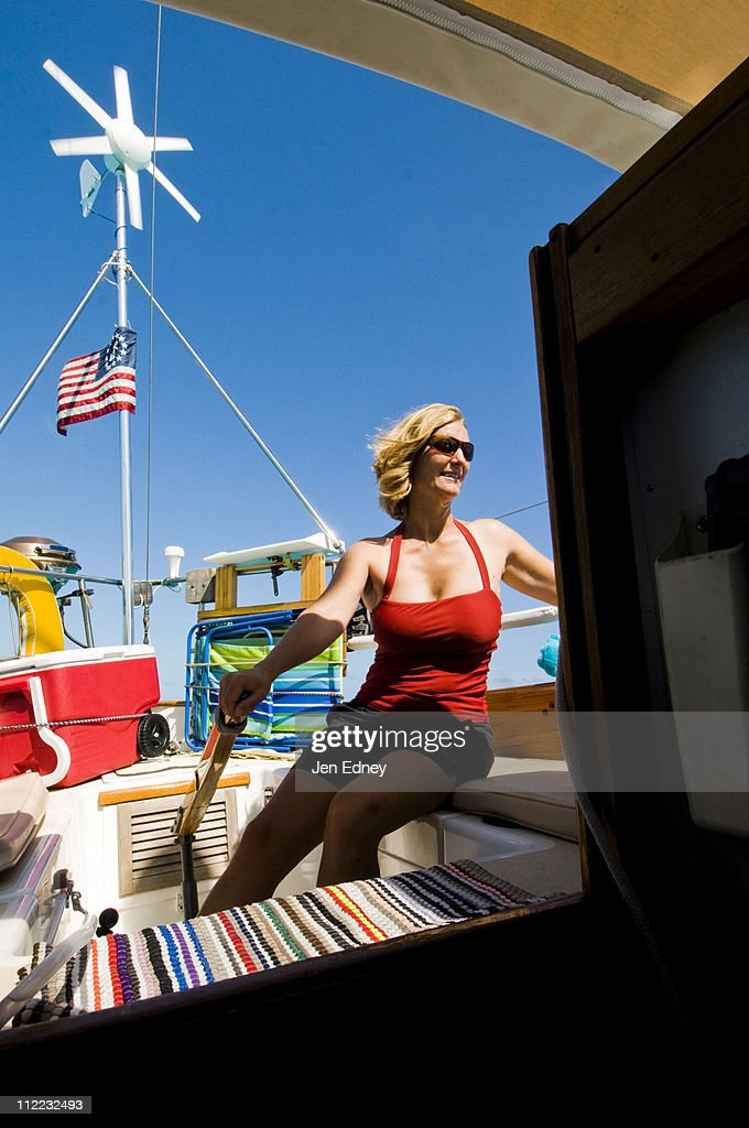 A woman in a red bathing suit gets some sun onboard a sail boat in the Bahamas.