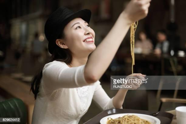 woman in a restaurant eating spaghetti