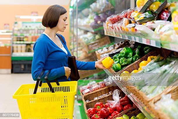 Femme dans un magasin envisager de légumes.
