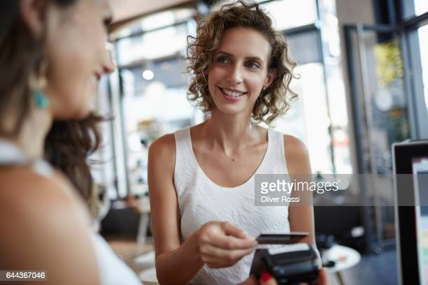 Woman in a shop paying with credit card