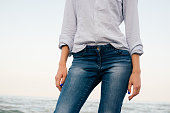 Details of women's clothing. A woman in a striped shirt and blue jeans standing on sea background.