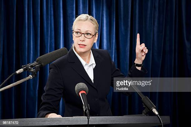 A woman in a suit speaking at a lectern