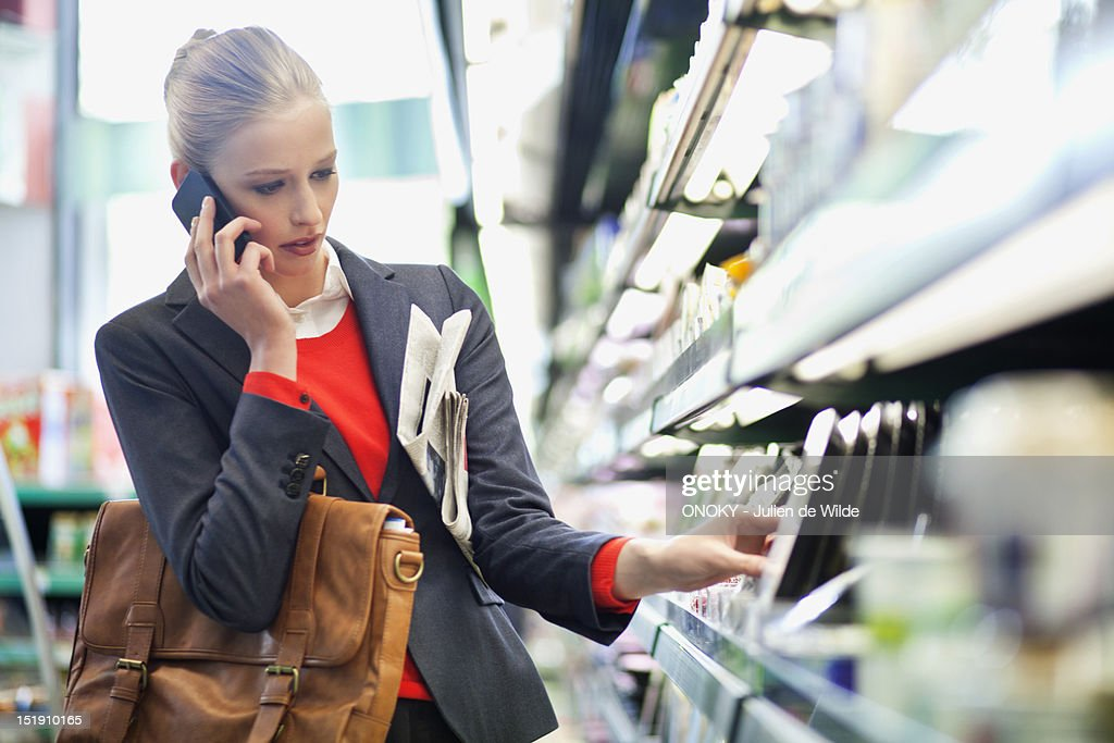 Woman in a supermarket talking on a mobile phone : Stock Photo