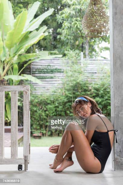 Woman in a swimming costume relaxing in a tropical villa