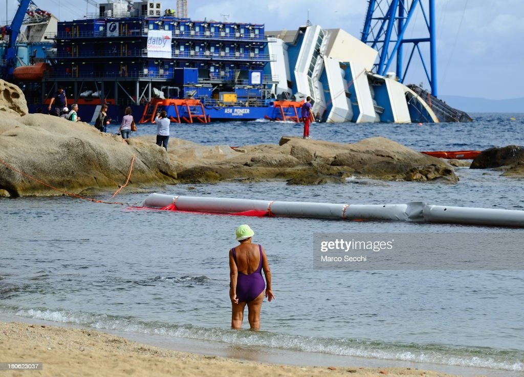 A woman in a swimsuit walks in front of the wreckage of the Costa Concordia on September 13, 2013 in Isola del Giglio, Italy. Work is expected to begin on September 16 to right the stricken Costa Concordia vessel. If the operation is successful, it will then be towed away and scrapped.
