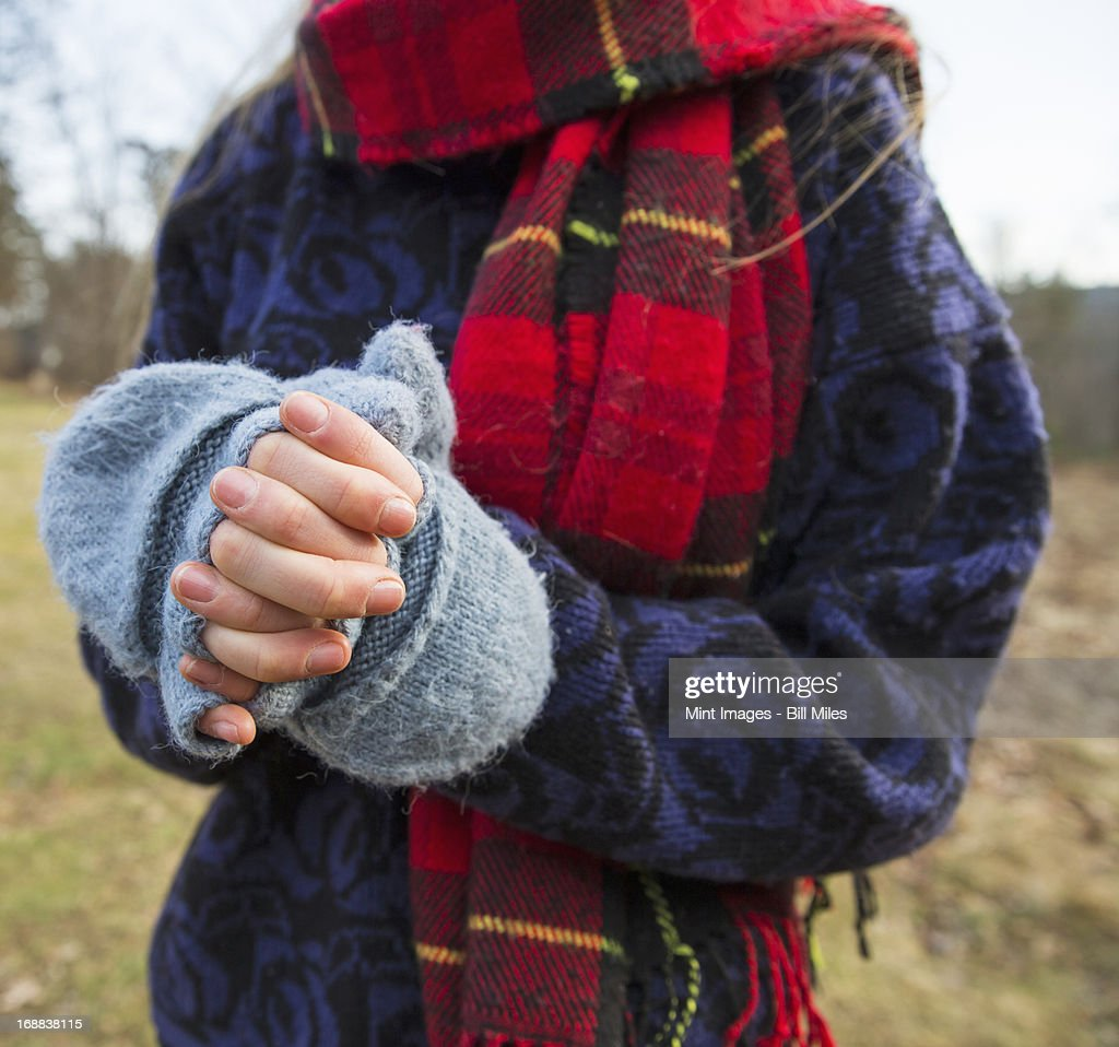 A woman in a tartan scarf and knitted woollen mitts, keeping her hands warm in cold weather. : Stock Photo