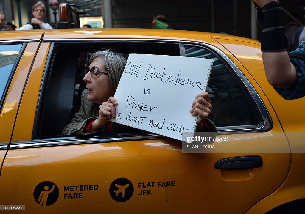 A woman in a taxi holds a sign as Occupy Wall Street protesters pass by September 17, 2012 on the one year anniversary of the movement in New York. Police in New York on Monday arrested at least a dozen demonstrators marking the one-year anniversary of the Occupy Wall Street movement, witnesses said. At least eight people were taken into custody when they tried to block an entrance to Wall Street, representatives of the National Lawyers Guild at the scene, told AFP. Others were arrested when they started moving from Zuccotti Park toward Wall Street as police on horseback blocked side streets on horseback, according to an AFP reporter at the scene. AFP PHOTO/Stan HONDA