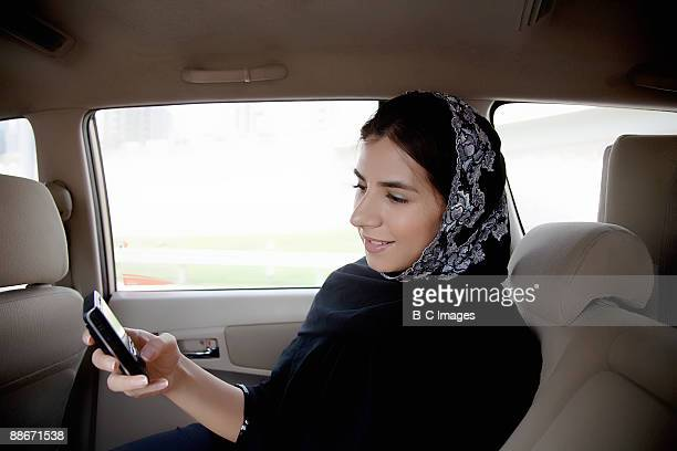 Woman in a taxi text messaging with a mobile phone, Dubai, UAE.