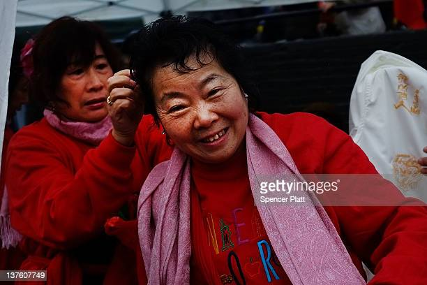 A woman in a traditional dance troupe has her hair adjusted in Chinatown in celebration of the Chinese New Year on January 23 2012 in New York City...
