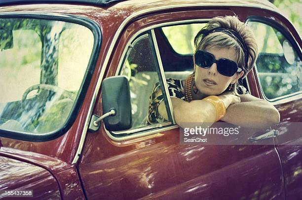 Woman in a vintage italian car. 1970s style.