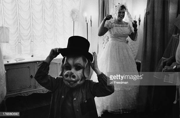 A woman in a wedding dress laughs at a child in a pig mask Helsinki 1985