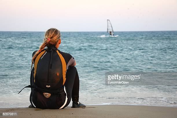 A woman in a wetsuit is watching the windsurfers in Prasonissi on July 20 2008 in Rhodes Greece Rhodes is the largest of the greek Dodecanes Islands