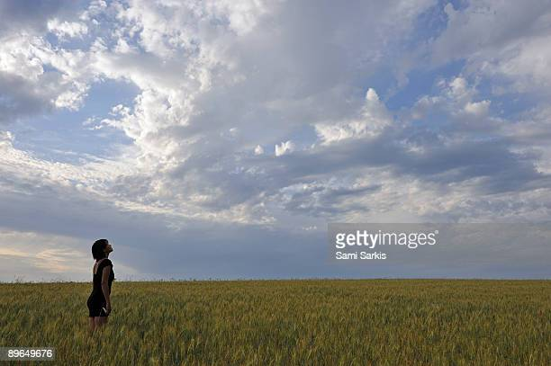 Woman in a wheat field, contemplating sunset