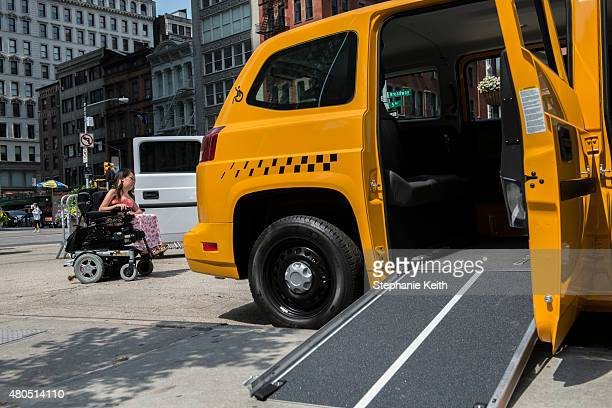A woman in a wheelchair rolls past a proposed taxi ramp designed for people with disabilities at the first annual Disability Pride Parade on July 12...