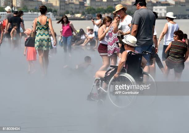 A woman in a wheelchair sit in the mist of the 'Mirroir d'eau' a reflecting pool of water in Bordeaux where temperatures came close to 40 C on July...
