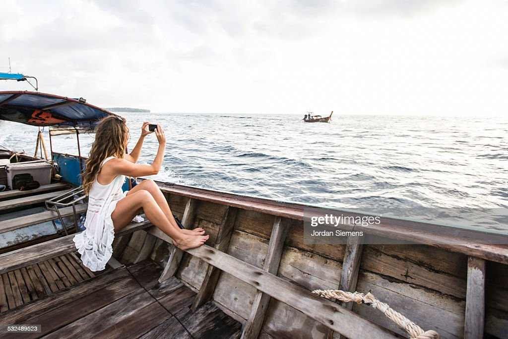 A woman in a white dress on a boat.