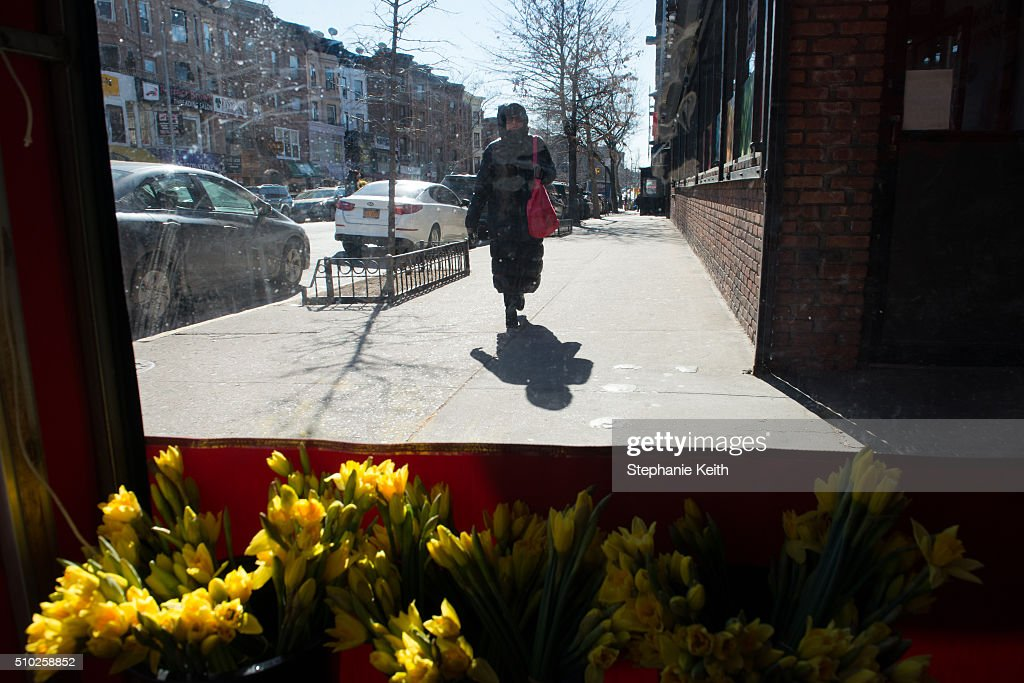 A woman in a winter parka walks past an indoor flower stand on February 14, 2016 in the Brooklyn borough of New York City. The city broke a 100-year record February 14, as emputures dropped minus 1 degree Fahrenheit.