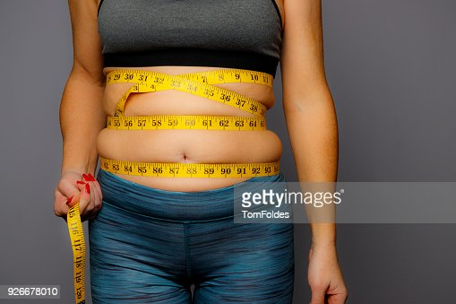 Woman in Active Wear With Squeezed Measuring Tape on a Gray Background : Stock Photo