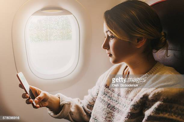 Woman in airplane with smartphone