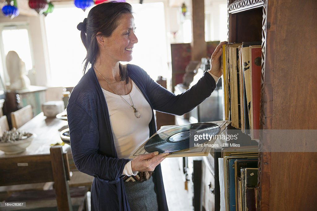 A woman in an antique store in a small town, with objects and furniture from the past. Looking at black vinyl records.