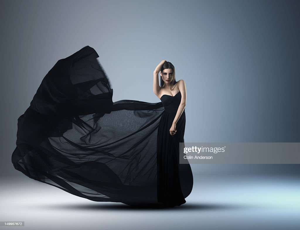 A woman in an evening dress with flowing fabric : Stock Photo