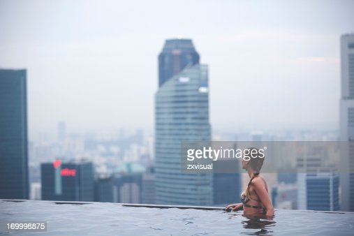 A woman in an infinity swimming pool overlooking the city