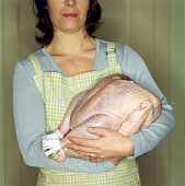 Woman in apron cradling uncooked turkey, close-up