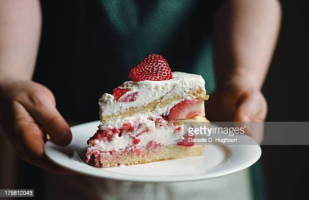 Woman in apron holding slice of strawberry cake